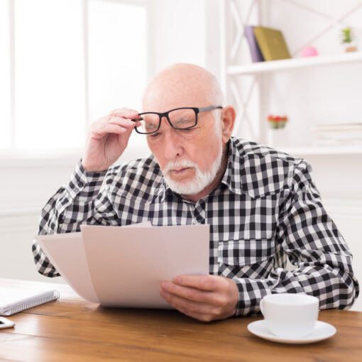 Shocked Senior Man Looking At Bills Copy Space